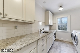 Laundry Room featuring stone floors, wall-to-wall built-in storage with granite counter and hanging storage, white subway tile backsplash, Whirlpool Duet Steam washer and dryer, 2 light fixtures and window overlooking rear yard