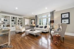 Living Room featuring hardwood floor, crown molding, baseboard moldings, designer pendant light fixtures,2 sets of built-in bookcases with open shelving and under storage, also accessible to 2nd Home Office.