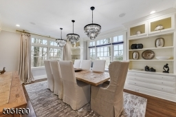 Dining Room featuring hardwood floors, baseboard molding, crown molding, built-in speakers, wall of triple windows with built-in window seat flanked by built-ins with open shelving and under storage, 3 chic chandeliers &recessed lights.