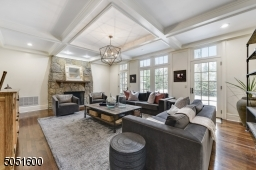 Family Room w/ access from front hall, Kitchen & Living RM featuring hardwood floors, baseboard molding, crown molding, coffered ceiling w/ recessed lights, chandelier, wall of windows overlooking patio & access to patio and stone (gas) fireplace