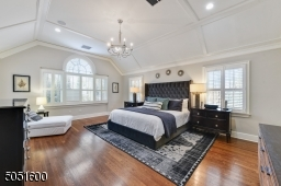Primary Bedroom w/ hardwood floors, baseboard molding, large palladium window w/ plantation shutters, vaulted tray ceiling w/ molding, large WIC w/ window, built-in speakers, 2 chandeliers, built-ins & open shelving, sitting area / home office