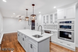 """Beautiful wood cabinetry, quartz counter tops & center island with a breakfast bar, butler's pantry and a 24"""" wine cooler"""