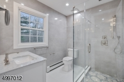 Gorgeous luxury master bath featuring a  large frameless glass enclosed Rain Shower
