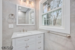 Full master bath with decorative porcelain tiles and wood vanity.