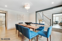 Dining Room is open to Foyer and features hardwood floors, deep baseboard moldings, triple double hung window, modern bubble chandelier, recessed lights, built-in speakers and custom drapes