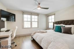 En-suite Guest Bedroom / Home Office featuring hardwood floors, deep baseboard moldings, two exposures of windows, double closet