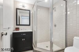 Full Bathroom featuring glass enclosed shower with grey subway tile, wood look ceramic grey floor tile, marble shower floor, custom vanity with marble top