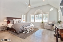 Primary Bedroom features double paneled privacy doors, triple palladium window, vaulted ceiling, hardwood floors, deep baseboard molding, ceiling fan, recessed lights and dressing area with 3 custom fitted closets (2 large walk-ins plus a lines closet)