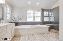 Primary Bathroom features vaulted ceiling, recessed lights, hanging chandelier, double sink vanity, stone floors, soaking tub with marble surround, seamless glass enclosed walk-in shower with built-in bench and private commode room w/ toilet