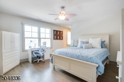 En-suite Bedroom features hardwood floors, baseboard moldings, walk-in closet, and 2 sets of double hung windows
