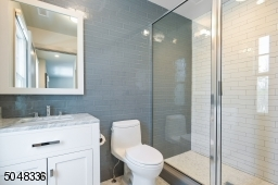 En-suite Bathroom features grey and white marble floor, walk-in glass enclosed shower with white and grey subway tile and vanity with grey marble top