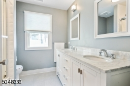 Hallway Bathroom features double sink wall-to-wall vanity with grey and white marble top and concealed under cabinet storage and shower over tub with sliding glass door and modern white textured tile
