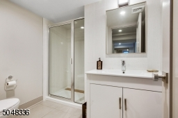 Full Bathroom featuring stone flooring, white vanity with white marble top, glass enclosed walk-in shower with subway tile