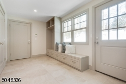 Mud Room featuring stone floor, built-in cubbies with under storage and bench, access to rear yard, walk-in coat closet / pantry and direct access to attached garage