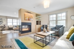 """Chic """"greige"""" hardwood floors throughout set the tone for this tremendous home. A stunning two-sided gas fireplace with built-ins and glass shelves make for seamless entertaining between the Living Room and Family Rooms."""