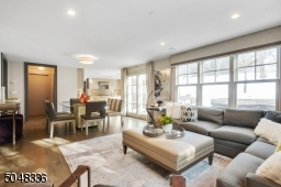 Family Room is open to the Kitchen & features hardwood floors, deep baseboard moldings, 2-sided gas fireplace w/ built-in shelves & flush cabinetry, recessed lighting, flush light fixture, two exposures of windows, double sliders to rear patio
