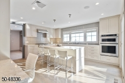 High-end appliances including KitchenAid double ovens, refrigerator, six-burner stove and Bosch dishwasher, undermount stainless steel sink with commercial style faucet and triple window overlooking rear yard, and built-in work space