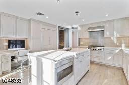 Features hardwood floors, deep baseboard moldings, granite counters, built-in speakers,double sliders to rear patio, custom light grey cabinetry, large island w/seating for 4, grey tile backsplash,recessed lights,under cabinet lights,high-end appliances