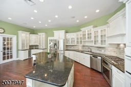 Custom cabinetry and wine refrigerator. Overlooks family room and backyard views.