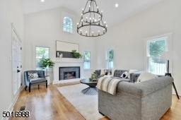 This 20 light wagon wheel chandelier makes a bold statement in the family room with cathedral ceilings, lots of natural light, new fireplace and french doors to bluestone patio.