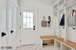 This custom designed mudroom with plenty of hooks and storage is conveniently located just off the driveway entrance with a white oak benchtop.  Be sure to check out the laundry area nestled behind the double doors.