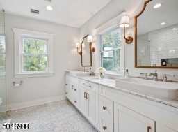 Enjoy the luxury of a marble bath with a 10ft long double vanity with marble countertops, oversized sinks, lots of natural light, a walk-in shower, custom shower glass, a large linen cabinet and Kohler plumbing fixtures.  Designed by Clear Space Home.