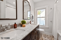 This well appointed full bathroom designed by Clear Space Home features a double vanity, marble countertops, Kohler plumbing, patterned hexagon tile, handmade-look subway tile and a large linen cabinet.