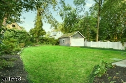 There is lots of space to hang out in this lushly landscaped backyard with bluestone patio, detached garage and newly paved driveway.