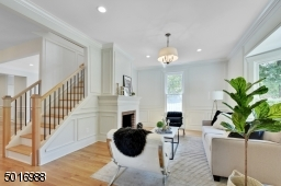 This formal living room has high ceilings, floor to ceiling wainscoting, original fireplace, new white oak floors and a new staircase with iron railings.