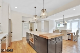This spacious open concept kitchen and dining room was designed by Clear Space Home with marble-look quartz, Thermador appliances, custom white oak details, double farm sink, subway backsplash and satin brass hardware.
