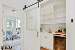 This walk-in pantry-bar area with barn door was designed by Clear Space Home with marble-look quartz, bar sink, beverage cooler, subway backsplash, satin brass hardware and tons of bonus storage.