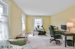Spacious bedroom with separate sitting area, hardwood floor under carpet