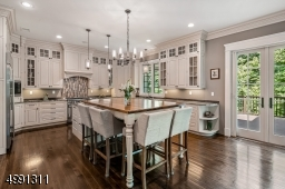 Today's favored white-hued cabinetry keeps things bright. Appliances include Wolf 6-burner range and microwave, Sub-Zero refrigerator/freezer with ice/water feature, Miele dishwasher.