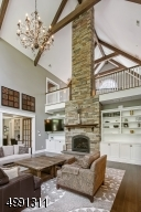 The soaring stone fireplace is flanked with bookcase and entertainment built-ins. Take in a heightened view of the architectural splendor from the open upper level.