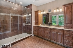 Wood custom vanity, marble counter top, mounted hutches. Oversize glass-enclosed shower. Plumbed for future soaking tub. Stone flooring.