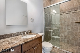 Bathroom accompanying 5th bedroom is handsomely turned out in stone and marble surfaces.