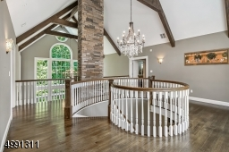 Swirled railing adds architectural interest in the loft as do the beamed volume ceiling and expansive windows.