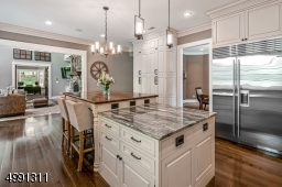 Extraordinary top-of the line granite. At the center island a granite prep area joins a raised butcher-block dining table with seating for four. Kitchen is open to the Great Room.