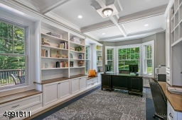 A coffered ceiling crowns the study. With a built-in desk and room for a free-standing second, the room can readily accommodate two busy planners. Walk-in bay window and single windows with window seats. Bookcases and cabinetry abound.