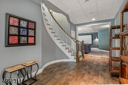 """Open floor plan is ideal for entertaining. Plumbing for future wet bar. Elegant """"tile-look"""" drop ceiling. """"Wood-Look"""" laminate tile flooring. Half bath, multiple storage closets, utility room. French doors lead to covered paver stone patio."""