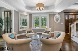 Open to the foyer, the living room offers arrivals unimpeded welcome. An octagonal tray ceiling is overhead.