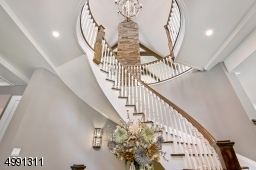 Solid wood 8-foot double entry doors open to the Foyer with dramatic curving staircase. Neutral wall palettes present a serene backdrop throughout. 10-foot ceilings on first level, 9-foot on second and walk-out lower.