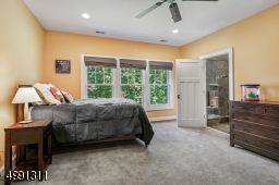 Spacious secondary bedroom with full bath, custom walk-in closet, attic access with pull-down stairs and hardwood flooring under plush wall to wall carpeting.