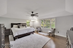 Large master bedroom with hardwood flooring, full bath and walk in closet.