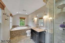 Master bath with jetted tub and seamless glass shower doors.