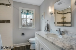 First floor full bathroom adjacent to a bedroom intended as private quarters for guests.