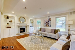 The Living Room features an attractive raised-hearth wood burning Fireplace with marble surround, custom wood mantel and is flanked by custom-designed cabinetry.