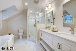 Luxury bath is goeorgeous and features a soaking tub, glass-enclosed large shower with decorative tiles and corner niches.