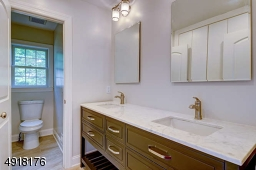 """The main bath on this level has a tiled floor; deep, built-in cubby """"linen"""" space; attractive double wood vanity with quartz countertop."""