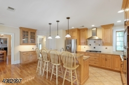 Large renovated kitchen boasts wood cabinets, center island, stainless steel appliances, wood floors with french door that leads to the deck